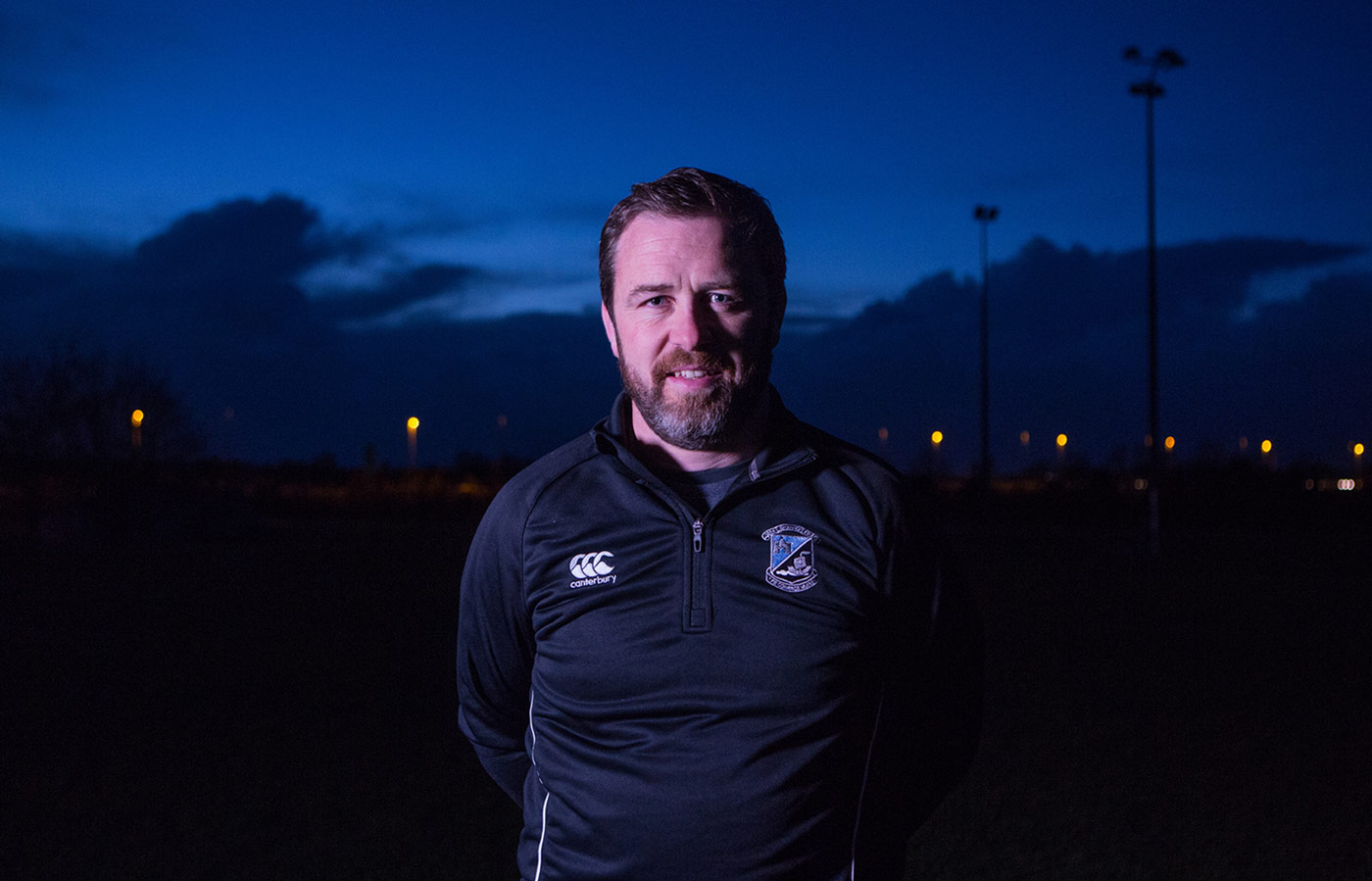 LIT video and photography production of man in sports uniform on a dark pitch