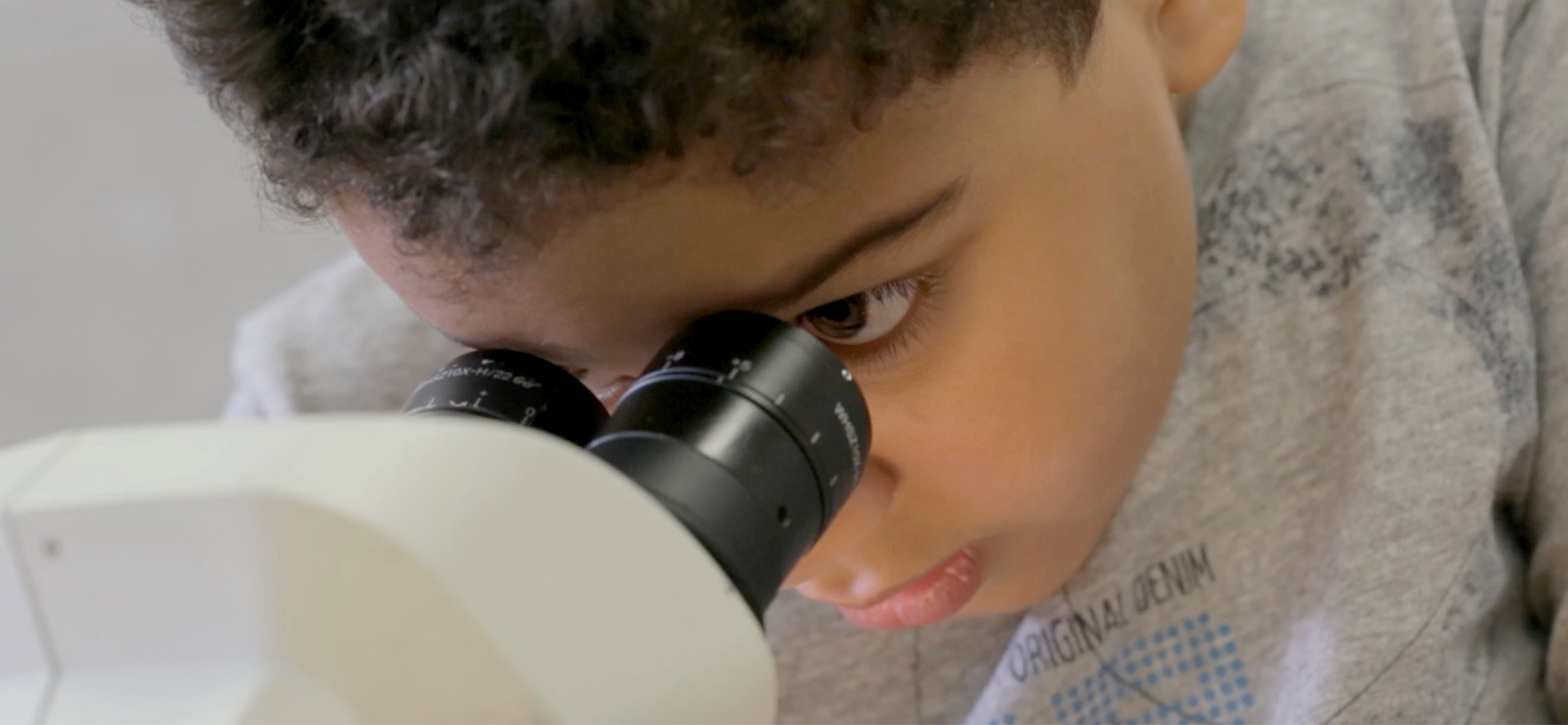 MIC video and photography production of young boy looking in a microscope