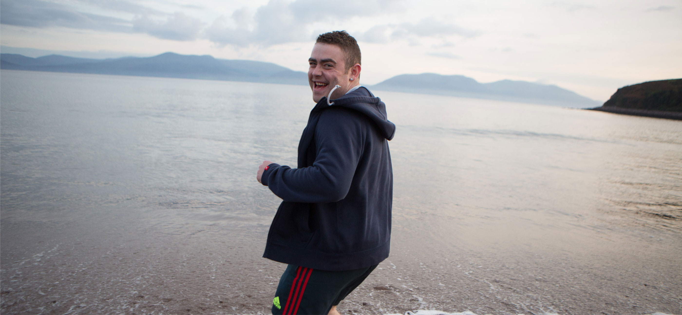 Novas photography production. Image of laughing man by the sea with mountains in background.