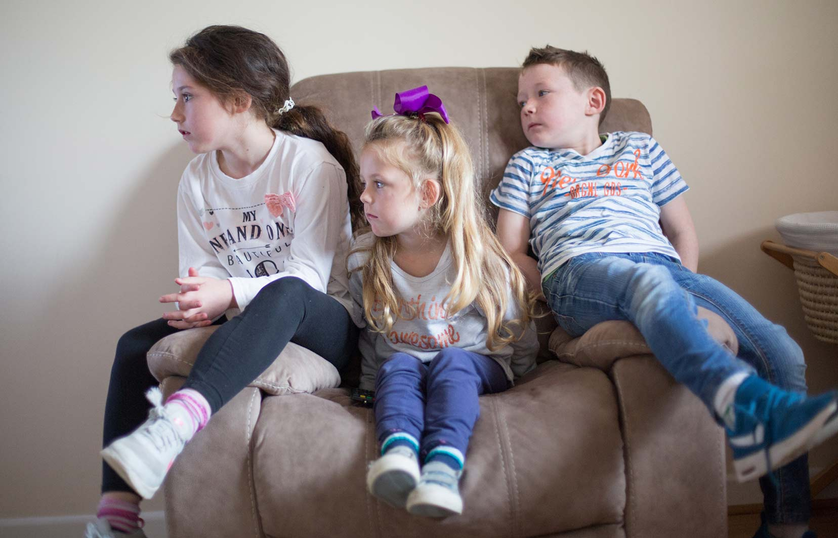 Novas video and photography production. Image of 2 girls and 1 boy on an armchair.
